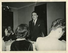 Young man Standing at a Table Addressing a Group