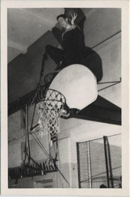 Ron Bannerman Sitting on Top of a Basketball's Basket