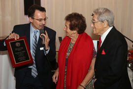 Lois and Stanley Tucker receiving a plaque from Eric Buzzetti