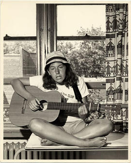 Young Woman Singing and Playing Guitar