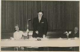 Man Standing at a Microphone and Cutting a Cake