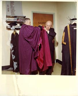 Henry F. Hall Putting on his Academic Regalia
